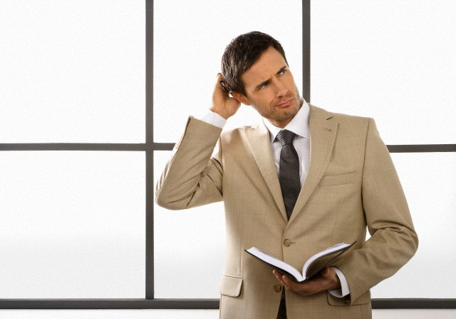 Businessman with date book, scratching his head